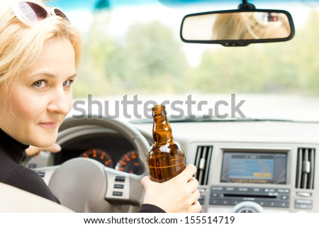Smiling female driver drinking alcohol from a bottle and turning to the passenger side and talking, completely losing all concentration on the road - stock photo