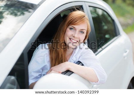 Smiling female driver looking out the car - stock photo