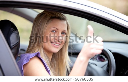 Smiling female driver with thumb up sitting in her car - stock photo