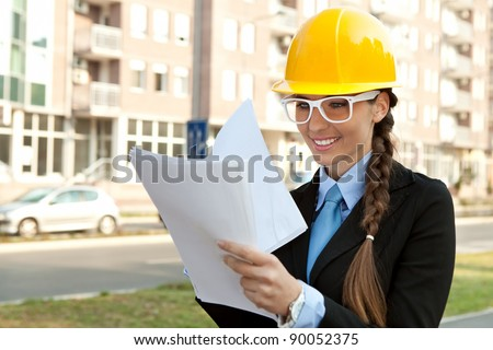 smiling female engineer with hard hat reading  blueprints, outdoor - stock photo