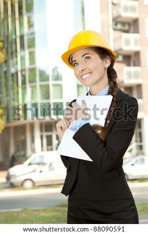 smiling female engineer with her project in background - stock photo