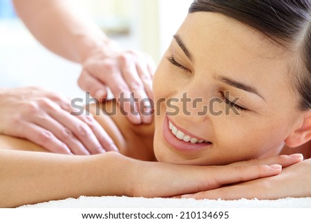 Smiling female enjoying massage in spa salon - stock photo