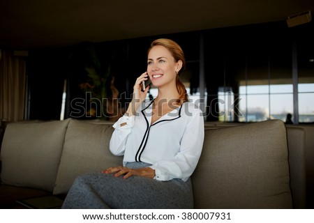 Smiling female entrepreneur talking on cell telephone with secretary while sitting in modern office interior, charming businesswoman enjoying a mobile phone conversation while waiting for her partners - stock photo