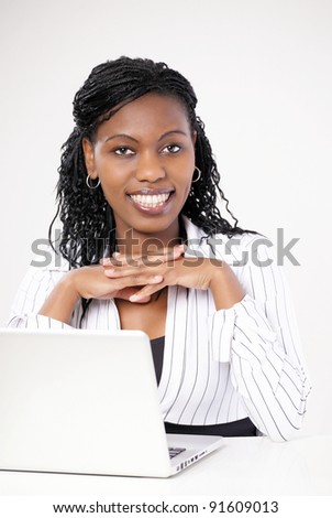 Smiling female executive with laptop looking at you - stock photo