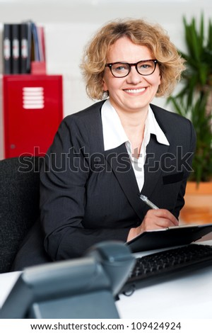 Smiling female executive writing notes on clipboard looking at you