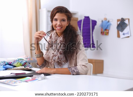 Smiling female fashion designer sitting at office desk