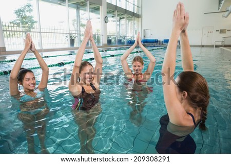Smiling female fitness class doing aqua aerobics in swimming pool at the leisure centre - stock photo