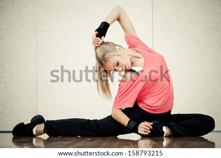 Smiling female fitness instructor in a gym - stock photo
