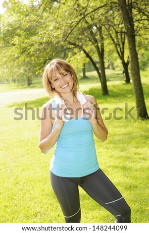 Smiling female fitness instructor standing with towel around neck after exercising in green park - stock photo