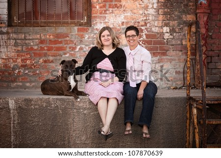 Smiling female friends with dog on old loading dock
