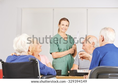 Smiling female geratric nurse standing with a group of senior people - stock photo