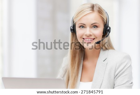 smiling female helpline operator with headphones and laptop - stock photo