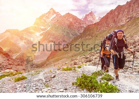 Smiling female hikers Two young smiling female travelers walking rocky path with hiking gear and backpacks with green grass and flowers on foreground and bright sunny mountain landscape on background  - stock photo