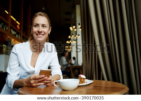 Smiling female holds mobile phone and looks for someone while relaxes in modern cafe during dinner, happy joyful woman student waits for call on cell telephone while sits in coffee shop during lunch - stock photo