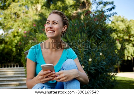 Smiling female is holding cell telephone while relaxing in the fresh air in summer day during free time, cheerful woman is dreaming about something good while is sitting with mobile phone outdoors - stock photo