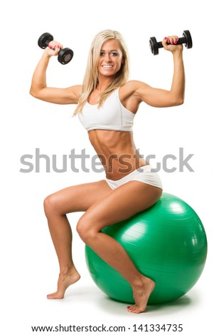 Smiling female lifting up a dumbbells seated on a fitness ball isolated on white background