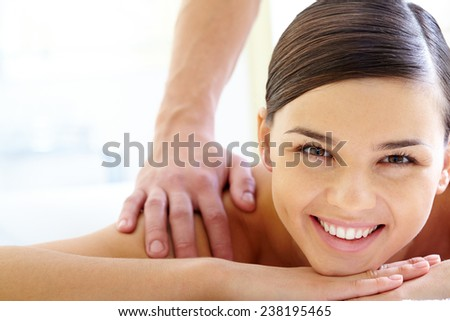 Smiling female looking at camera during massage - stock photo