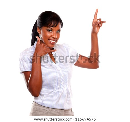 Smiling female looking at you and pointing up while saying call me on isolated background - stock photo