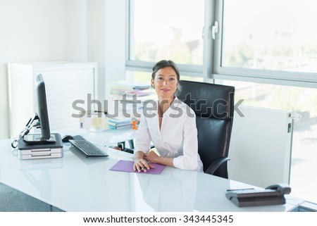 Smiling female manager looking at camera in her white office Woman sitting at a glass desk in front of a black computer She is wearing a white shirt her hair are tied Her hands are crossed on a folder