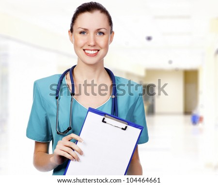 Smiling female medical doctor with clipboard in a corridor of a hospital. - stock photo