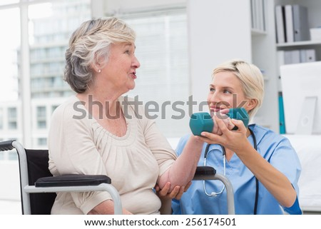Smiling female nurse looking at senior patient while assisting her in lifting dumbbell in clinic - stock photo