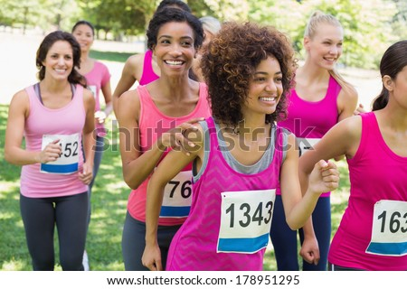 Smiling female participants of breast cancer marathon running in park - stock photo