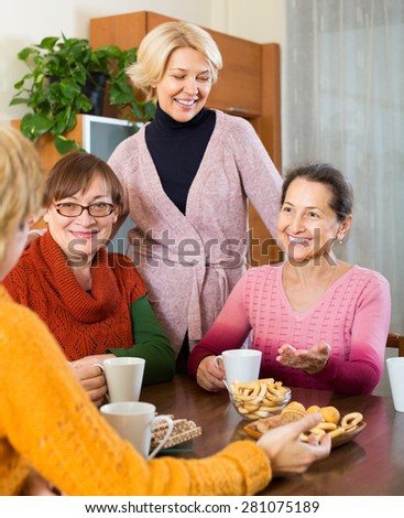 Smiling female pensioners drinking coffee and talking at home  - stock photo