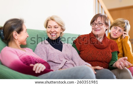 Smiling female pensioners sitting on sofa and talking - stock photo
