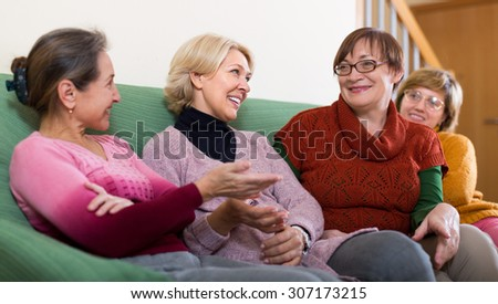 Smiling female pensioners sitting on sofa and talking. Focus on blonde - stock photo