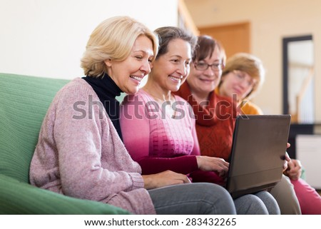 Smiling female pensioners working with notebook using wifi on sofa