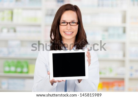 Smiling female Pharmacist shows an tablet computer at the drugstore - stock photo
