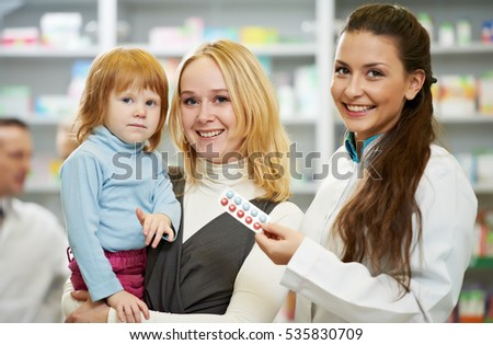Smiling female pharmacy seller with vitamins, mother and child