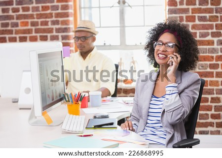 Smiling female photo editor using mobile phone in the office - stock photo