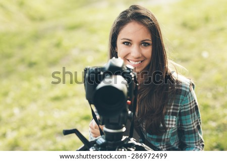Smiling female photographer using a professional digital camera on a tripod, natural landscape on background - stock photo