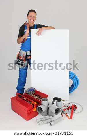 Smiling female plumber with panel for message - stock photo