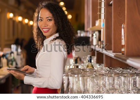 Smiling female pub owner with digital tablet looking at camera - stock photo