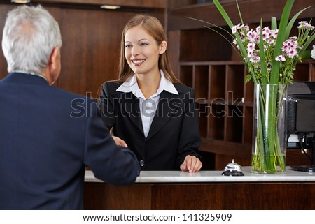 Smiling female receptionist greeting a senior guest with handshake - stock photo