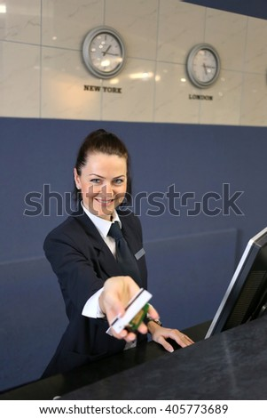 smiling female receptionist passing card to guest - stock photo