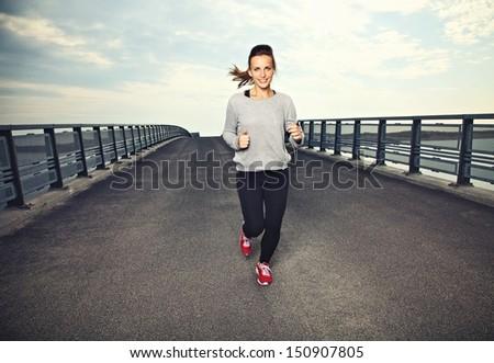 Smiling female runner doing running exercise - stock photo