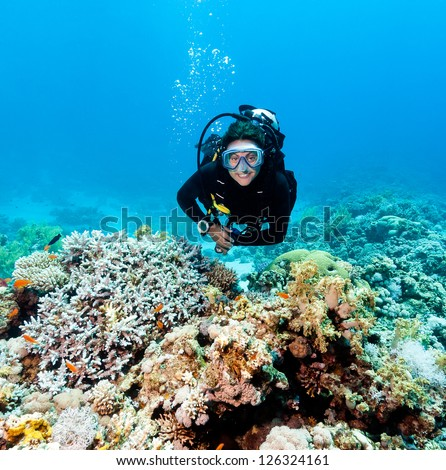 Smiling female scuba diver underwater on a coral reef - stock photo