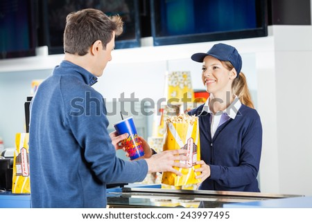 Smiling female seller giving popcorn paperbag and drink to man at concession stand in cinema - stock photo