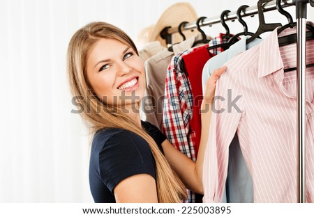 Smiling female shopper choosing shirt at clothing rack in retail store. Young beautiful blond Caucasian model buying clothes in fashionable boutique.  - stock photo