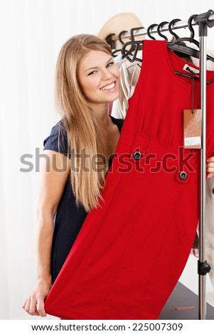 Smiling female shopper trying new dress in shopping boutique.  Portrait of lovely Caucasian woman model holding elegant clothes in retail store.   - stock photo