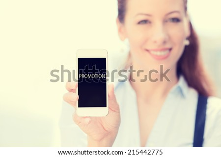 Smiling female showing mobile smart phone with promotion sign on screen, isolated outside city background, focus on smartphone. Advertisement concept. Positive human emotions, new technology event - stock photo