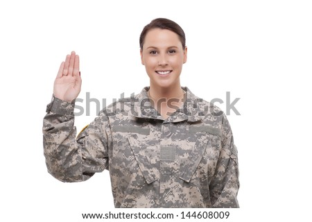 Smiling female soldier holding up right hand  - stock photo