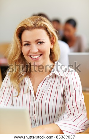 Smiling female student at laptop in university class - stock photo