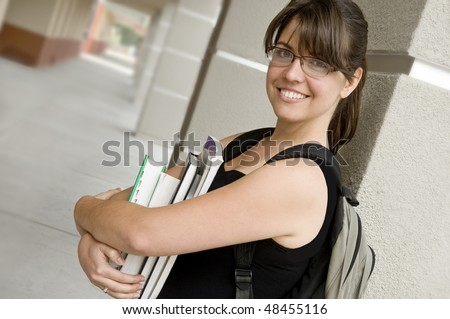 smiling female student, holding books, wearing a backpack, outdoors at school - stock photo