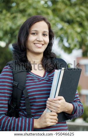 Smiling female student holding text books - stock photo