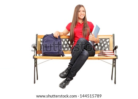 Smiling female student sitting on a wooden bench and holding a notebook isolated on white background