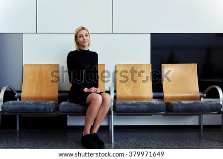 Smiling female student waiting for classmates in hallway before start lectures in University, charming woman dressed in elegant clothes sitting in office interior before meeting with entrepreneur - stock photo